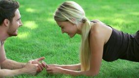 Sprawności fizycznej kobiety szkolenia deski ćwiczenia wpólnie trenera lying on the beach na trawie w parku zbiory wideo
