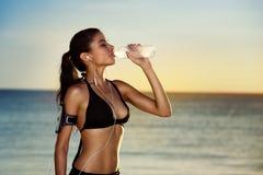 Sprawności fizycznej kobiety woda pitna po ćwiczyć na letnim dniu w b zdjęcia stock