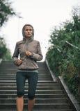 Sprawności fizycznej młoda kobieta jogging w dżdżystym mieście Obraz Stock