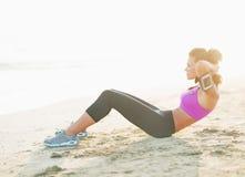Sprawności fizycznej młoda kobieta robi brzusznemu chrupnięciu na plaży Fotografia Stock