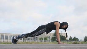 Sprawności fizycznej młodej kobiety atleta robi deski ćwiczeniu na stadium zbiory wideo