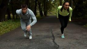Sprawności fizycznej para przygotowywająca dla biegać rasy na drewnianym przejściu na plenerowym parku zbiory