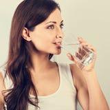 Sprawności fizycznej silna szczęśliwa uśmiechnięta kobieta pije czystą wodę z zdrową skórą i długim kędzierzawym włosy Zbli?enie  obraz stock