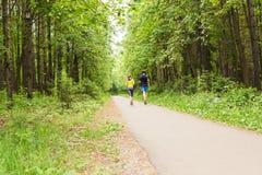 Sprawności fizycznej, sporta, przyjaźni i stylu życia pojęcie, - uśmiechnięta para biega outdoors Zdjęcie Royalty Free