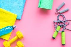 Sprawności fizycznej tło Wyposażenie dla gym i domu Skok arkana, dumbbells, expander, mata, woda na pastelowych menchii tła wierz Fotografia Stock