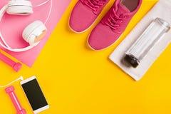 Sprawności fizycznych akcesoria na żółtym tle Sneakers, butelka woda, słuchawki i dumbbells, zdjęcie royalty free