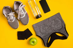 Sprawności fizycznych akcesoria na żółtym tle Sneakers, butelka wody, mądrze i sporta wierzchołek, obraz stock