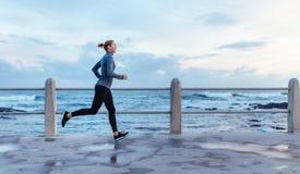 Sprawności fizycznej kobiety bieg na drodze morzem Zdjęcia Stock