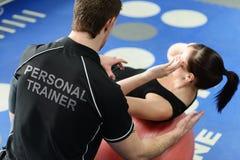 Sprawność fizyczna instruktora pomaga dziewczyna przez chrupnięć Fotografia Royalty Free