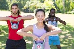 Sprawności fizycznej grupowy pracujący out w parku z czajników dzwonami Fotografia Stock