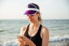 Sprawności fizycznej kobieta odpoczywa na plażowym słuchaniu muzyka z telefonem Zdjęcia Royalty Free