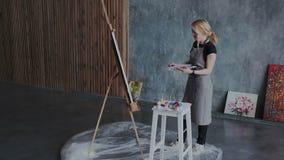 Sprawny żeński malarz pracuje w sztuk współczesnych przestrzeniach Ona obrazu obrazek na sztaludze używać gęste akrylowe farby