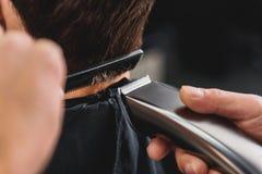 Sprawny fryzjer męski używa shearer dla ostrzyżenia Zdjęcia Royalty Free