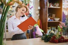 Sprawny kwiatu sklepowy asystent komunikuje telefonem Zdjęcia Stock