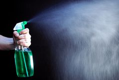 Spray. Hand holding green bottle and spraying liquid Stock Images