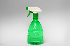 Spray bottle. Green spray bottle made of clear plastic on grey background Royalty Free Stock Photo