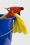 Spray bottle in blue bucket. Spray bottle and yellow rubber glove in blue bucket isolated against a white background Royalty Free Stock Images