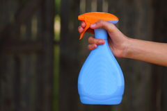 Spray Bottle. A close up view of someone holding a blue and orange plastic spray bottle Stock Image