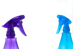 Spray bottles face. Two spray bottles facing each other against solid white background Stock Images