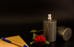 Spray bottles and roses with note book and pen. For perfume products Royalty Free Stock Photos