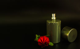 Spray bottles and roses. With for perfume products on black background Stock Image