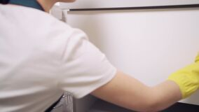 Spray cleaner on a white surface. Wipe the cabinet door with a cleaning cloth.