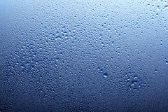 Spray des blauen Wassers auf Glas Stockbild