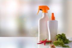Spray des Lichtschutzes zwei auf Glastisch mit Meerespflanze und Starfish Lizenzfreies Stockfoto