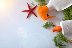 Spray des Lichtschutzes zwei mit Starfish auf die Glastischoberseite Stockfotografie