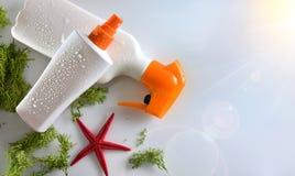 Spray des Lichtschutzes zwei mit Starfish auf Draufsicht des Glastischs Stockbild