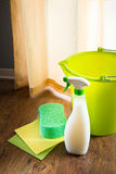 Spray detergent for wooden surfaces. Spray detergent with green bucket, sponge and pads on living room hardwood floor royalty free stock photos