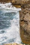 Wave crashes against eroded limestone rocks at Dwejra Bay, Gozo, Malta. Spray, foam and droplets - a wave crashes against the eroded limestone rocks of Dwejra stock photos