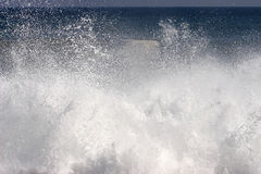 Spray and foam from wave hitting the shore Royalty Free Stock Images