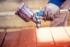 Spray gun getting paint over timber. Young painter renovating Stock Photos