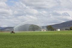 Spray Irrigator with Farm House in Background Stock Photography