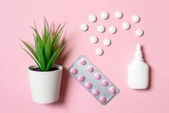 Spray nasale bianco con le compresse e le erbe su fondo rosa come trattamento di erbe del concetto di congestione, della sinusite immagine stock