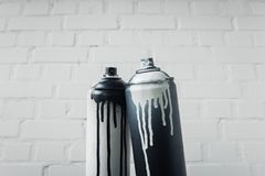 Spray paint in cans with brick wall background. Close up view of spray paint in cans with brick wall background royalty free stock photography