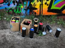 Spray paint cans for graffiti on floor. In front of graffiti mural stock photo