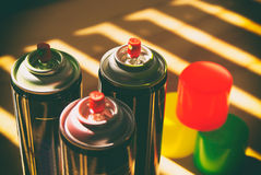 Spray paint cans. Photograph of some spray paint cans on a wood table royalty free stock photos