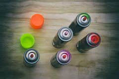 Spray paint cans. Photograph of some spray paint cans on a wood table royalty free stock photo