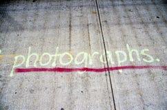 Photographs Graffiti. Spray paint graffiti on concrete sidewalk saying photographs stock image