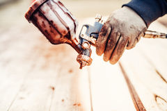 Spray paint gun and worker hand Royalty Free Stock Photos