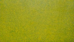 Spray paint in yellow green on canvas background Royalty Free Stock Photos