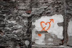 Spray Painted Heart on the Wall. Symbol of heart red sprayed on the bumpy wall royalty free stock photography