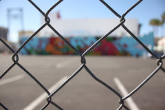 Spray painted wall through fense Royalty Free Stock Images