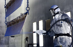 Spray painter. Man in a protective suit, wearing a gas mask spray painting steel semi finished parts in a production environment Royalty Free Stock Photo