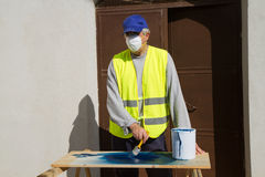 Spray painter. Painting a gate Royalty Free Stock Photo