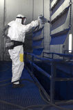 Spray painting room. Man, wearing a gas mask and a paper protective suit with respiration aid spray painting semi finished metal parts in a factory Stock Image