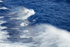 Spray rainbow of the Ocean Waves Stock Photos