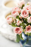 Spray roses. Romantic setup with coffee and roses in vase Stock Photo